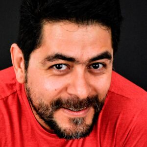 A man smiling, with black hair, beard and moustache. Wearing a red t-shirt.
